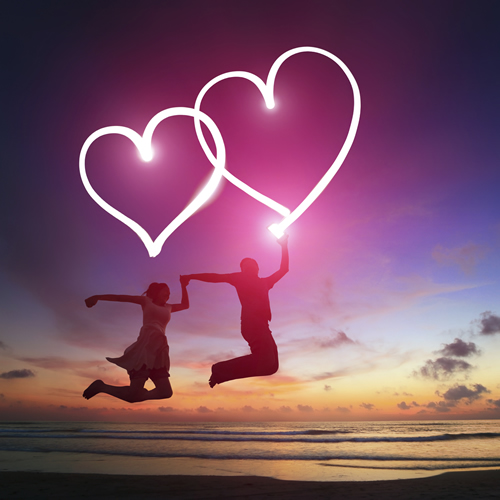 couple-with-glowing-hearts-jumping-at-beach-after-sunset
