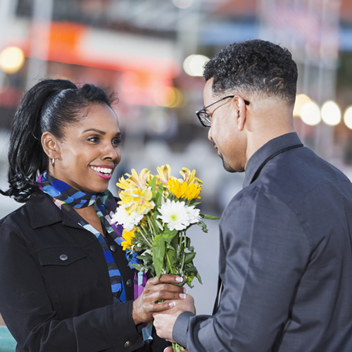 man-giving-flowers-to-young-latino-woman_500x500