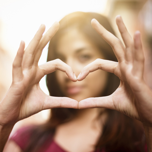 young-brunette-forms-heart-shape-with-her-fingers_500x500