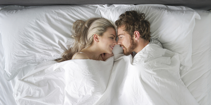 young-couple-in-bed-looking-at-eachother